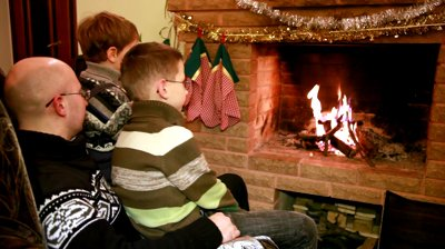 father-in-glasses-and-two-son-sitting-by-fireplace-and-watch-fire